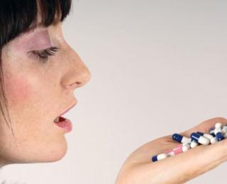 Девушка с таблетками в руке